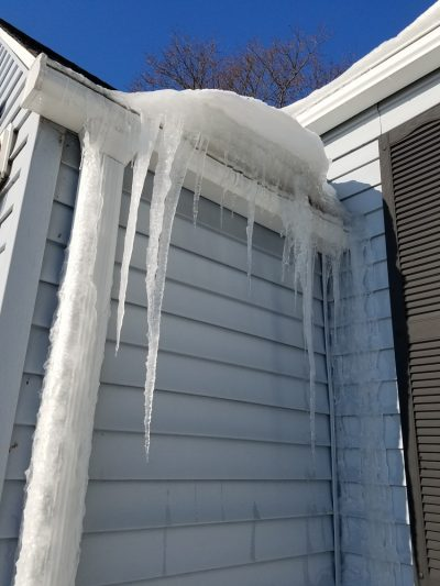 home roof covered in snow, icicles, and ice dams