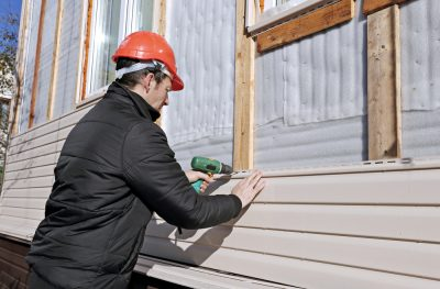 What is CertainTeed Monogram Siding? | TruHome Inc. (photo of vinyl siding being installed)